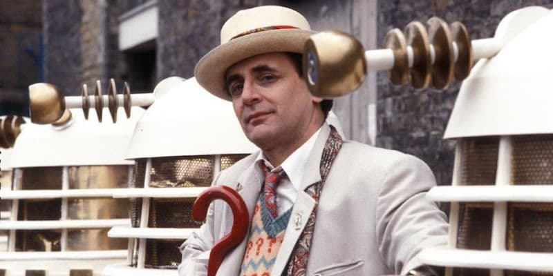 Sylvester McCoy among a row of Daleks carrying his umbrella
