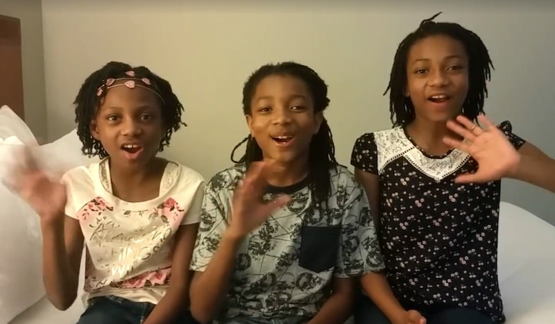 Brooklynn, Kaden and Nya Johnson waving at the camera in a video