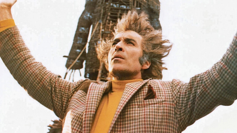 Christopher Lee holding up his hands in front of a large wicker man in The Wicker Man