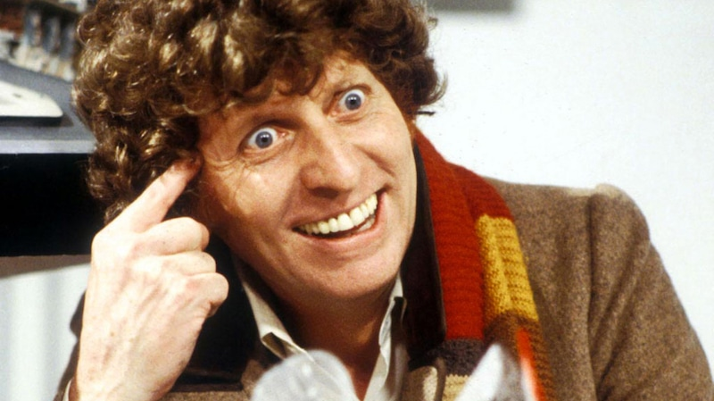 Tom Baker smiling as Doctor Who wearing his red, brown and yellow scarf
