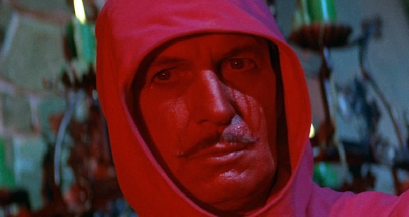 Vincent Price in a red hood and a painted-red face in The Masque of the Red Death