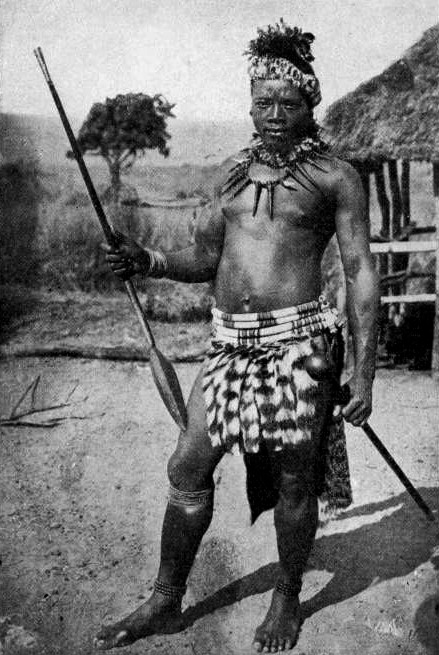 A black and white photo of a Zulu warrior with a iklwa