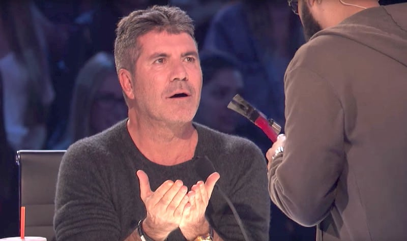 Simon Cowell looking afraid as Eric Jones holds a hammer on America's Got Talent