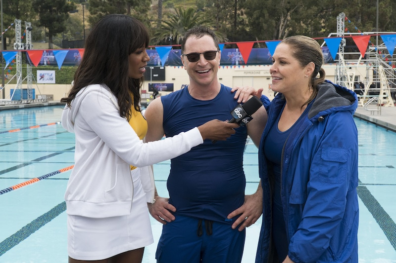 Cari Champion holding a microphone up to Malina and McCormack by the pool