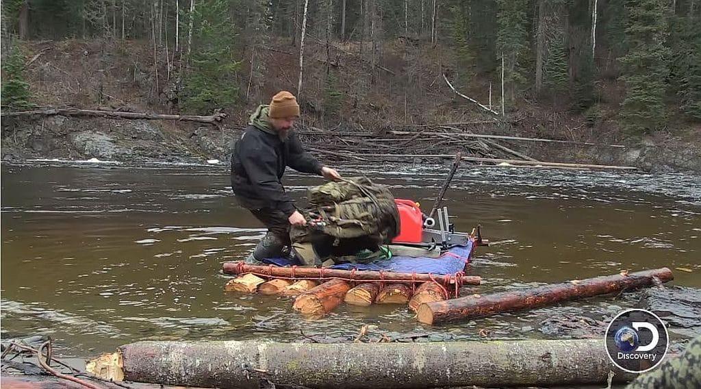 Boyce loading his raft in the river