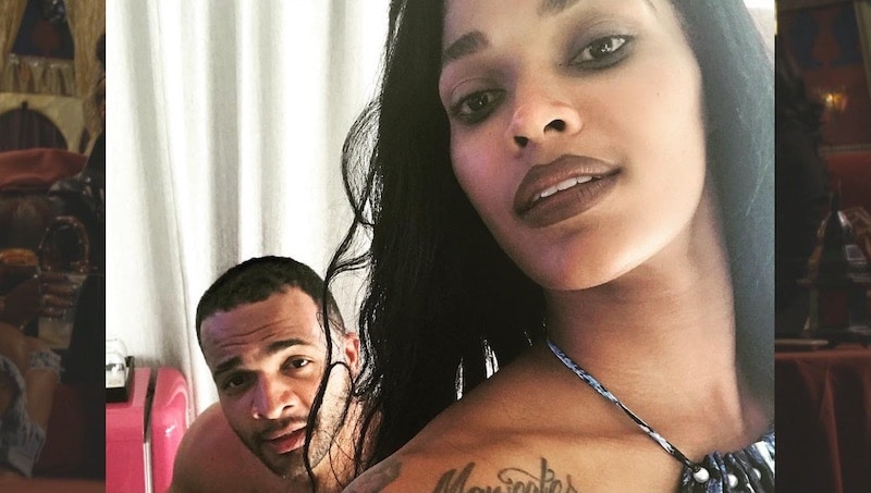 Joseline Hernandez standing in front of a man with his top off, with a 'Maneater' tattoo on her shoulder