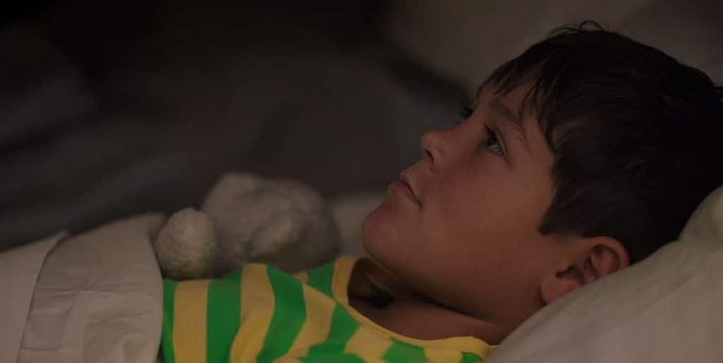 Ethan Kent as Ralph lying on a bed in Room 104