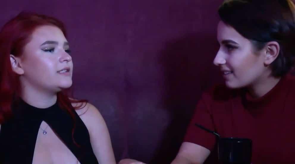 Megan talks to a friend in the club, both sitting