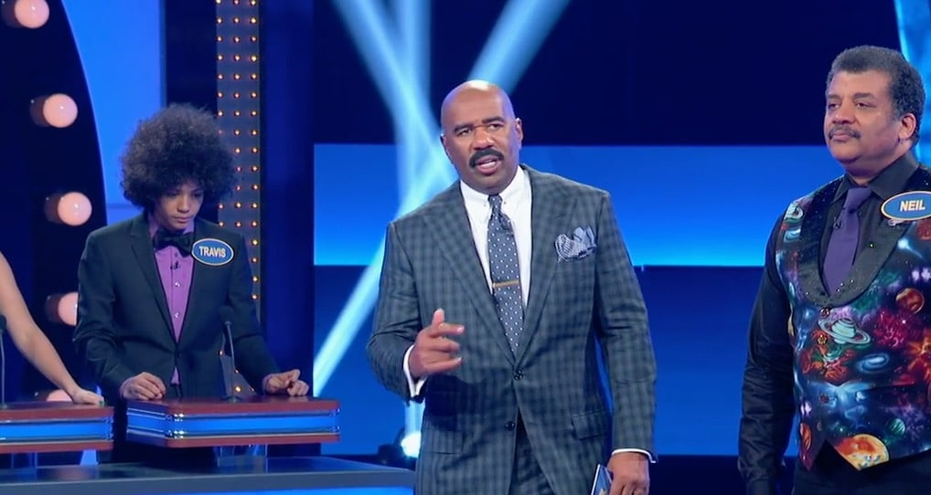 Neil deGrasse Tyson stands looking serious as he prepares to answer questions on Celebrity Family Feud