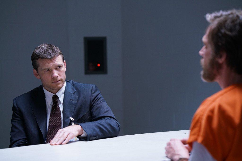 Sam Worthington as Jim Fitzgerald, sitting across a table from Paul Bettany's Kaczynski