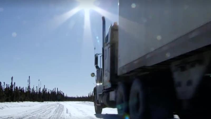 Photo of truck driving on the ice road in blazing sun