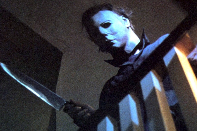 Michael Myers looking down a stairwell while holding a knife in Halloween