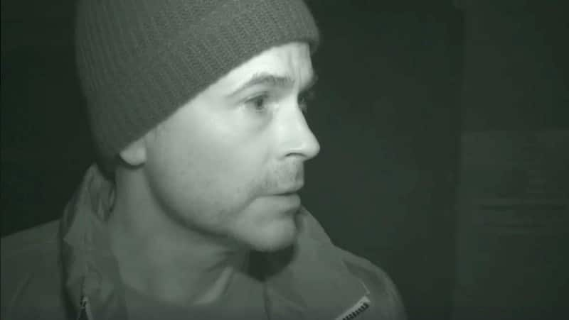 Rob Lowe inside Preston Castle at night with a light shining on his face on The Lowe Files