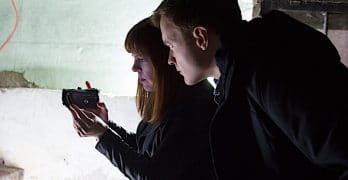 Adam Berry looks at the viewfinder of Amy Bruni's handheld camera