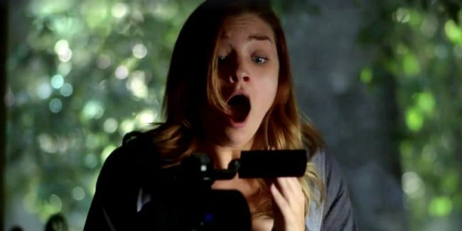 A scene from Evil Things showing a woman screaming at something she sees on a camcorder