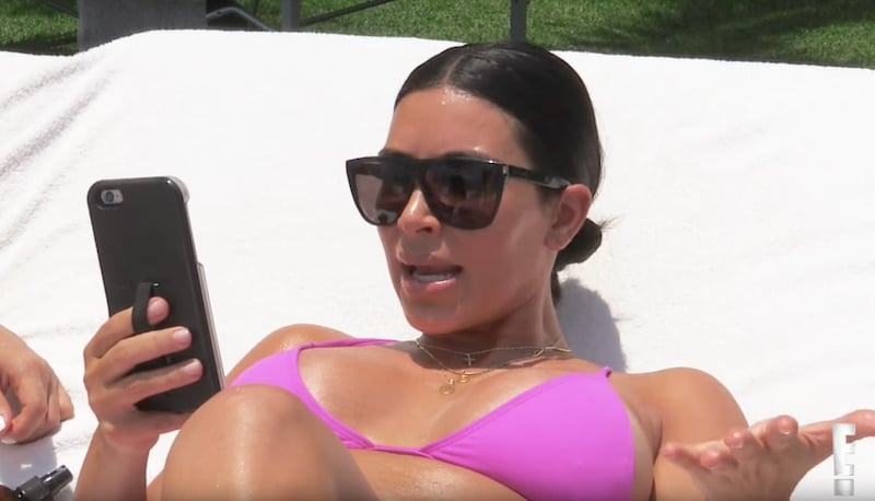 Kim looking at a phone while lying on a sunbed on Keeping Up with the Kardashians