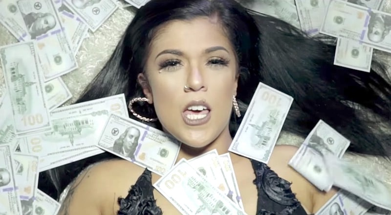 Emily Fernandez covered in money in the Gettin Rich video