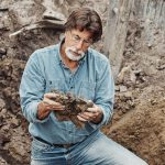 Rick examines an object inside a hole in The Curse of Oak Island Season 5