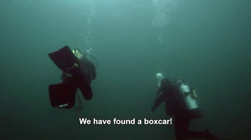 Footage of divers underwater, as one of them says 'we found a boxcar!'