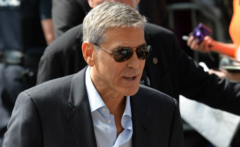 George Clooney wearing a black suit jacket and sunglasses.
