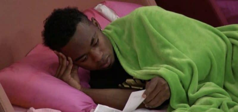 Swaggy C laying under a green blanket in the pink bedroom on Big Brother 20