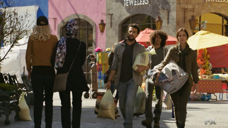 Still image:Mayans M.C. Búho/Muwan. Emily and Dita (Ada Maris) pass Adelita as she carries new clothes for Cristobal. Pic credit: FX
