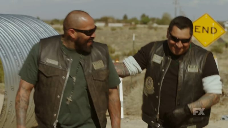 Still image from Mayans M.C. Escorpión/Dzec preview. Sgt-At-Arms Hank claps Gilly on the back as they laugh at the driver's struggle to free himself from the car wreck. Pic credit: FX
