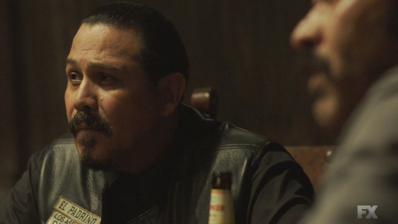 Still image from Perro/Oc. Alvarez tasks his Santo Padre charter to focus on finding the identity of the rebel leader.