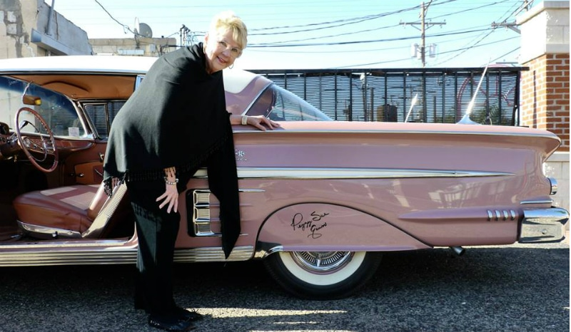 Peggy Sue Gerron poses with a pink Cadillac autographed with her name