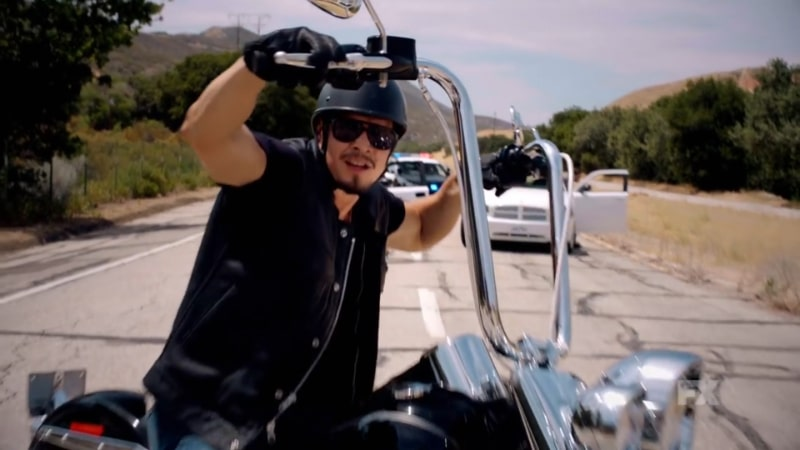 Still image from Mayans M.C. Cucaracha/K'uruch preview. EZ Reyes brings his motorcycle to a halt as police surround him. Pic Credit: FX