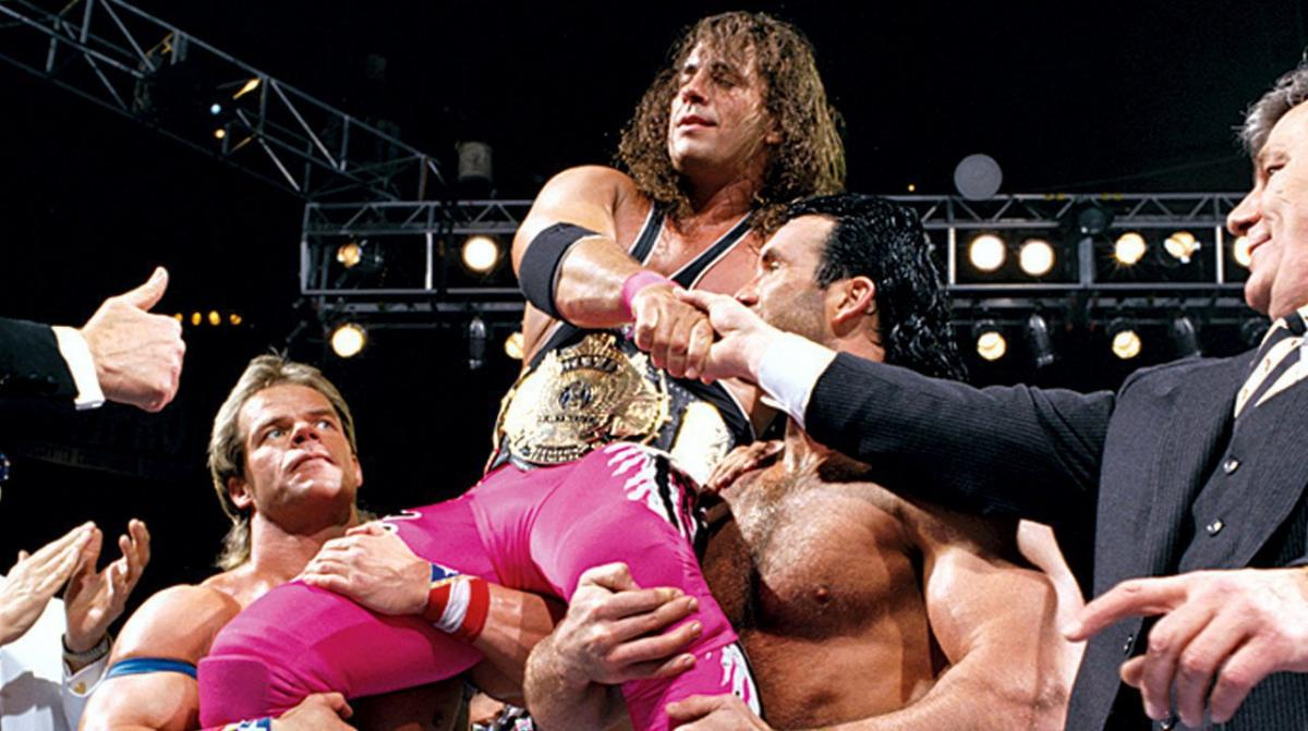 Bret 'The Hitman' Hart is carried by fellow wrestlers as he shows off his title belt