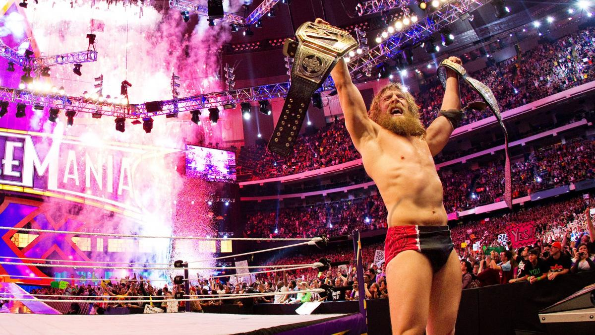 Daniel Bryan holding two title belts in the WWE