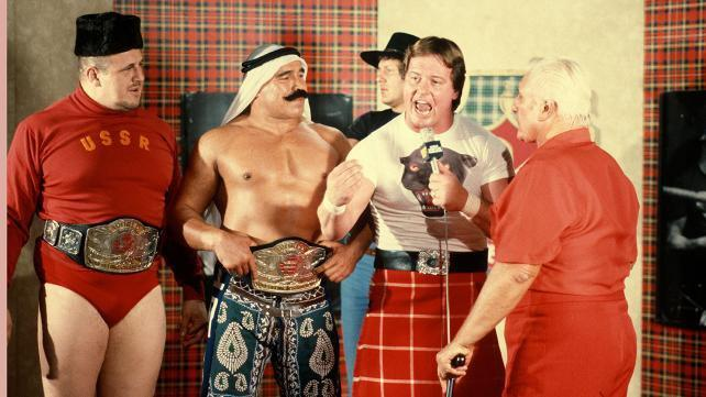 Rowdy Roddy Piper on the microphone flanked by the Iron Shiek and Nikolai Volkoff