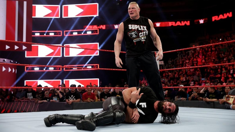 Brock Lesnar standing over Seth Rollins in the WWE ring