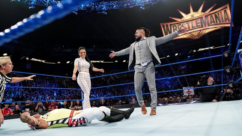 Andrade Cien Almas in the WWE ring with Rey Mysterio on the mat