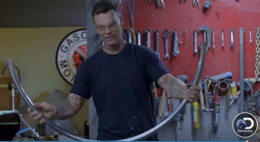 Chad Hiltz bends a shower rod to use it as part of a car door
