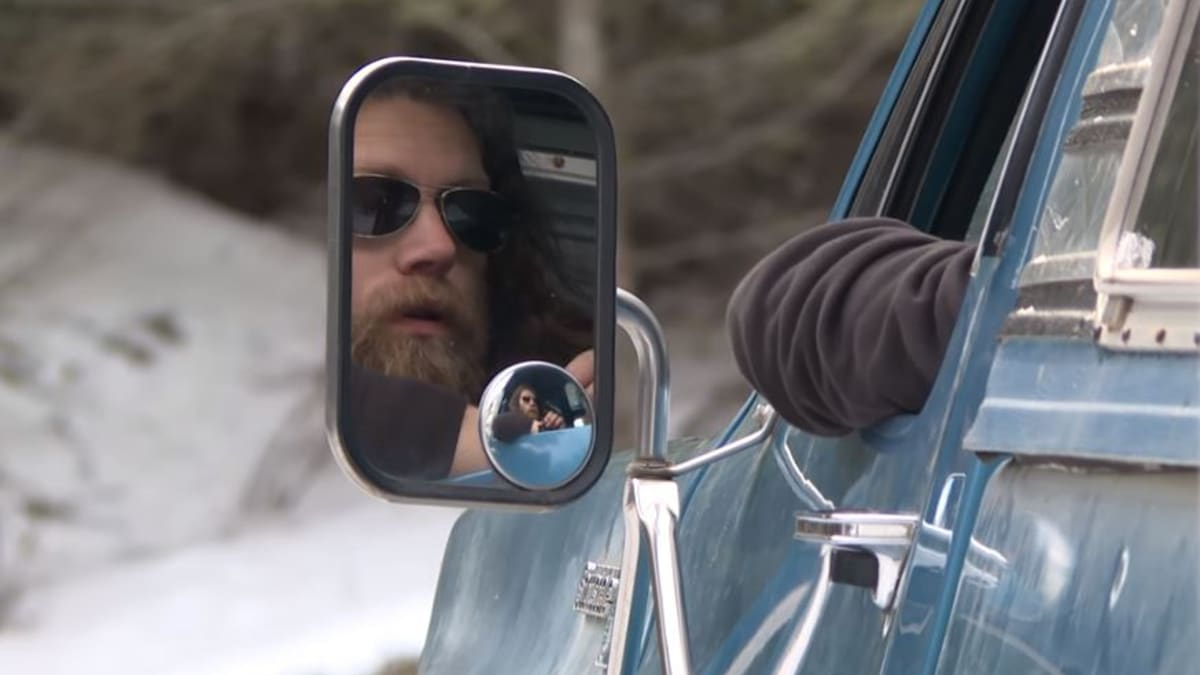Bam looking into the side mirror of his truck on Alaskan Bush People
