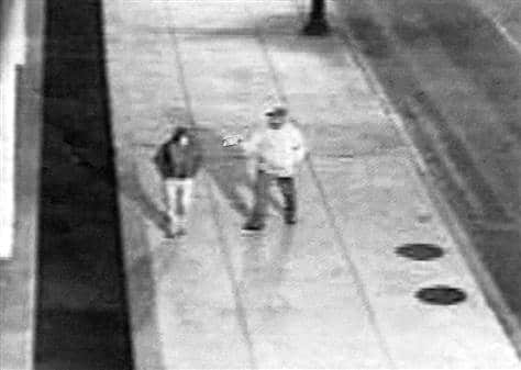 Black and white capture from CCTV footage showing a man pointing a gun at a woman