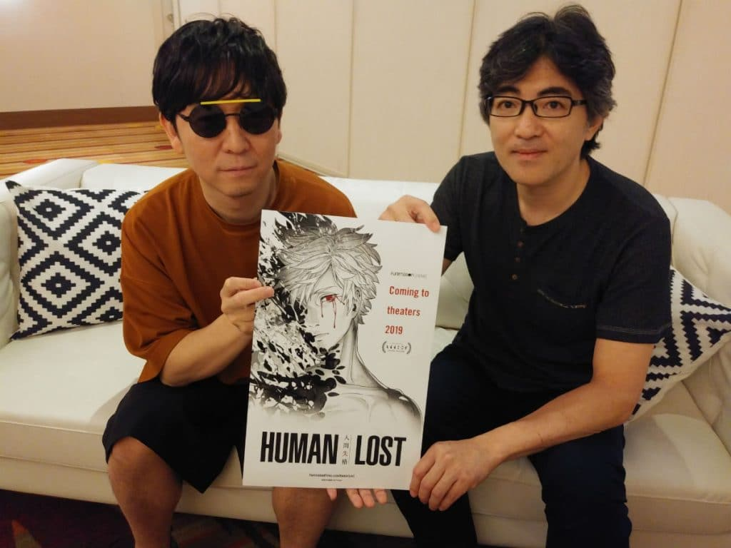 Taku Takahashi (left) and Fuminori Kizaki (right) at Anime Expo 2019 holding a Human Lost poster.
