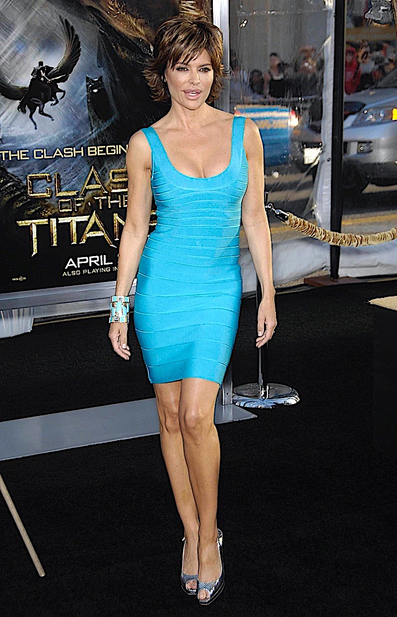 Lisa standing in front of a poster for the Clash of the Titans movie, she is in a bright blue dress.