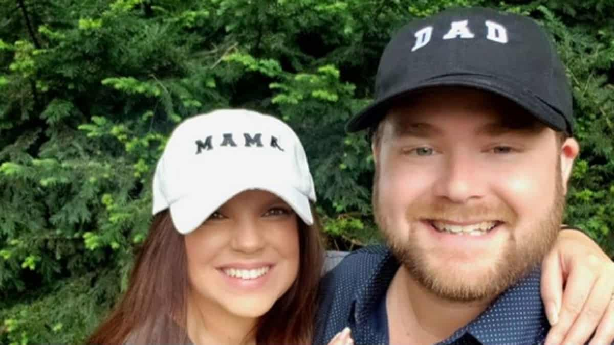 Amy and Dillon King wearing mom and dad hats.