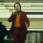 Joaquin Phoenix walking through subway in full Joker makeup.