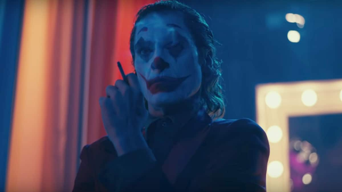 Joaquin Phoenix in full Joker transformation smoking a cigarette.