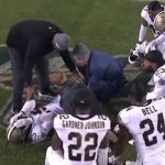 saints players gather around eli apple following his injury