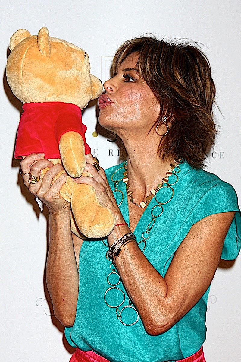 LIsa kissing a teddy bear in a fun photo, she is wearing a turquoise top