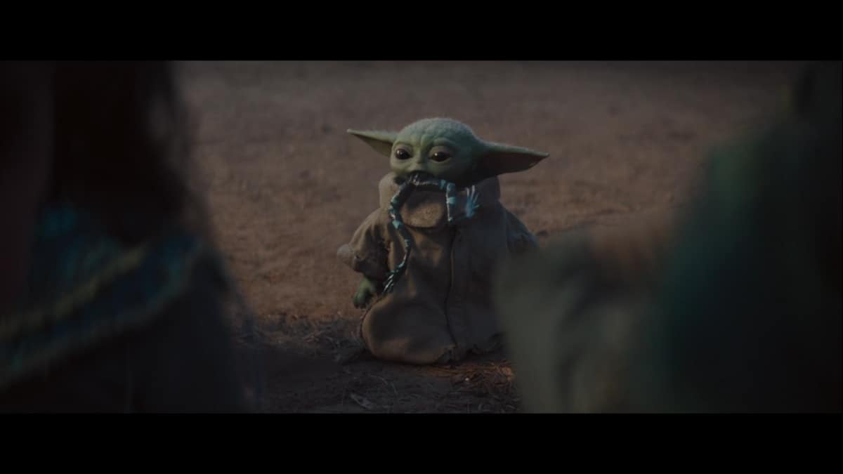 Baby Yoda attempting to eat a space frog on The Mandalorian