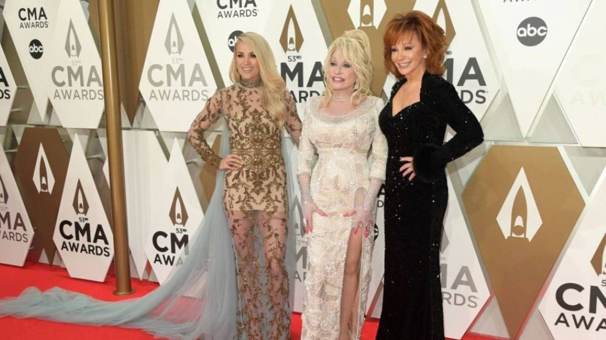 Carrie Underwood, Dolly Parton, and Reba McEntire pose on the red carpet
