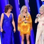 Carrie Underwood, Dolly Parton, and Reba McEntire on-stage at the CMA Awards.