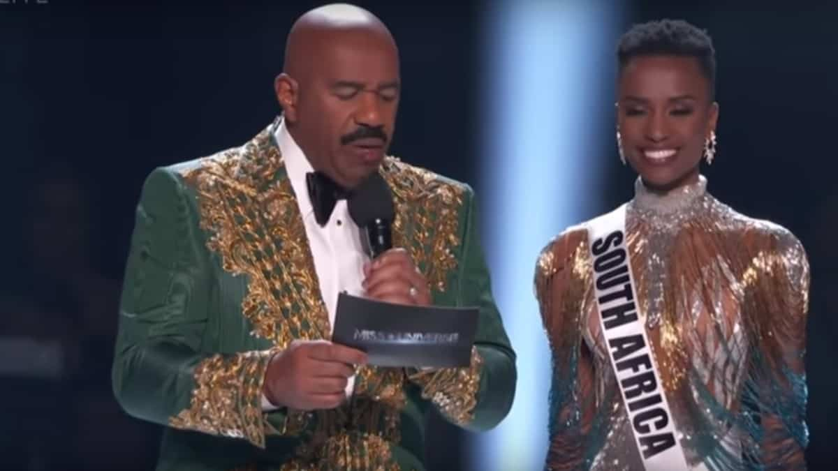 Steve Harvey on stage with Zozibini Tunzi, winner of Miss Universe 2019