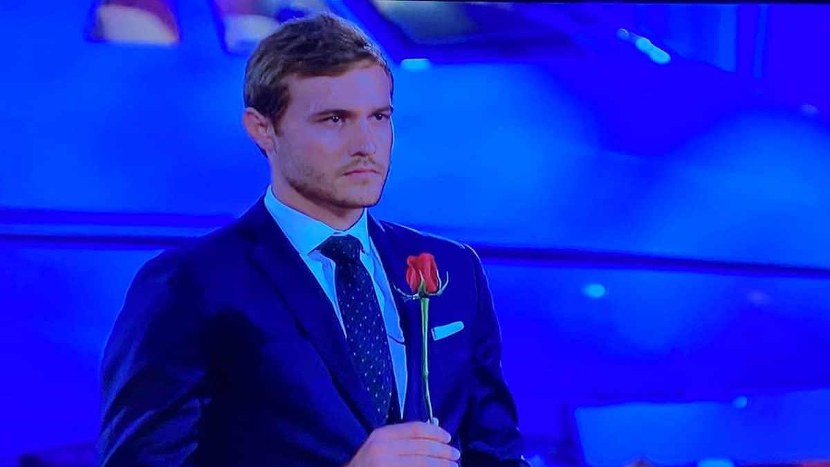 In Episode 8 of The Bachelor, Peter Weber, stands alone holding a rose